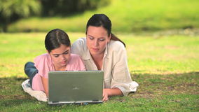 Mother and daughter using a laptop outdoors Royalty Free Stock Images