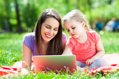 Mother and daughter using laptop outdoors Stock Photography