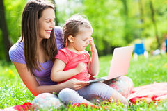 Mother and daughter using laptop outdoors Royalty Free Stock Photography