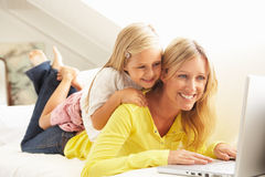 Mother And Daughter Using Laptop Relaxing On Sofa Royalty Free Stock Image
