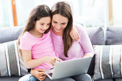 Mother and daughter using laptop Stock Photos