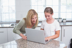Mother and daughter using laptop together Stock Image