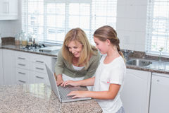 Mother and daughter using laptop together Stock Images