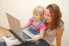 Mother and Daughter Using Laptop on wooden  floor Stock Photo