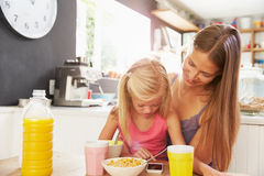 Mother And Daughter Using Mobile Phone At Breakfast Table Stock Images