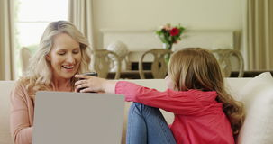 Mother and daughter using mobile phone in living room