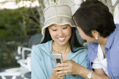 Mother and daughter using mobile phone smiling outdoors Royalty Free Stock Photo