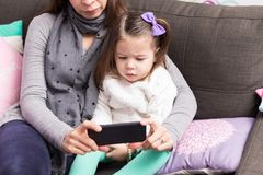Mother And Daughter Using Mobile Phone On Sofa. Female toddler watching movie with mom on smartphone while sitting on sofa at home stock image