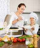 Mother and daughter using multicooker Stock Image