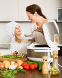 Mother and daughter using multicooker Royalty Free Stock Images
