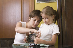Mother And Daughter Using Old Sewing Machine. Mother and little daughter using old sewing machine in home Stock Photo