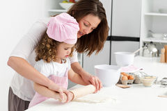 Mother and daughter using a rolling pin together Stock Images
