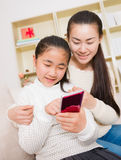 Mother and daughter using smart phone Stock Image