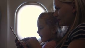 Mother and daughter using smartphone in airplane. Slowmotion of mother and daughter using smartphone in airplane stock video