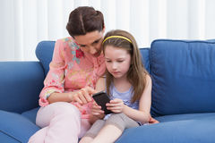 Mother and daughter using smartphone on couch Royalty Free Stock Photo