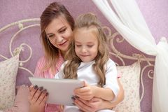Mother and daughter are using a tablet computer royalty free stock images