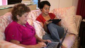 Mother and daughter using tablet computer together at home stock footage
