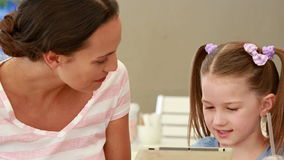 Mother and daughter using tablet computer together. In a restaurant stock footage