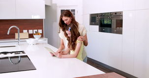 Mother and daughter using tablet in the kitchen. At home stock footage