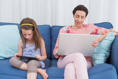 Mother and daughter using tablet and laptop Royalty Free Stock Photo