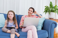 Mother and daughter using tablet and laptop Stock Photo