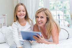 Mother and daughter using tablet pc in the bed Stock Images
