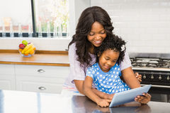Mother and daughter using tablet pc. In the kitchen Stock Photo