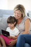 Mother and daughter using video game player Stock Photography