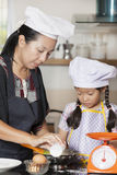 Mother and daughter using whisk to mix egg and wheat flour Stock Image