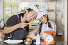 Mother and daughter using whisk to mix egg and wheat flour Stock Photography