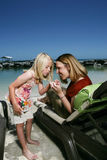Mother daughter on vacation. Adult woman and young girl looking at something in the girl's hand at the beach, caucasian/white Stock Photography