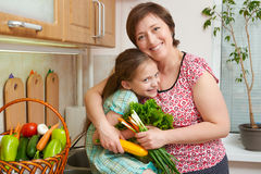 Mother and daughter with vegetables and fresh fruits in kitchen interior. Parent and child. Healthy food concept Royalty Free Stock Image
