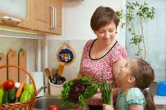 Mother and daughter with vegetables and fresh fruits in kitchen interior. Parent and child. Healthy food concept Stock Photography
