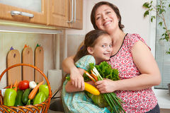 Mother and daughter with vegetables and fresh fruits in kitchen interior. Parent and child. Healthy food concept Royalty Free Stock Photos