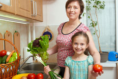 Mother and daughter with vegetables and fresh fruits in kitchen interior. Parent and child. Healthy food concept Royalty Free Stock Images