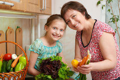Mother and daughter with vegetables and fresh fruits in kitchen interior. Parent and child. Healthy food concept Stock Image