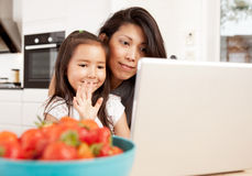 Mother and Daughter in Video Chat. Mother and daughter using computer, waving while in a live video chat Royalty Free Stock Photos