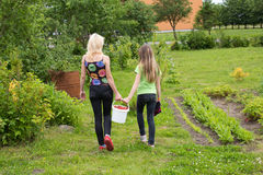Mother and daughter walk home from the garden Stock Images