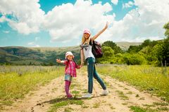 Mother and daughter walk on road through field Royalty Free Stock Photo