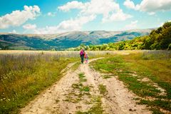 Mother and daughter walk on road through field Royalty Free Stock Photos
