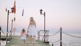 Mother and daughter walk on wooden pier at sunset. Mother and daughter walkin on wood pier at sunset near sea stock video footage