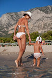 Mother and daughter walking along the beach. Royalty Free Stock Image