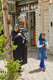 Mother and daughter are walking along city street, Kashan, Iran. Kashan, Iran - April 27, 2017: A Muslim woman, dressed in religious clothing, walks along the Stock Photo