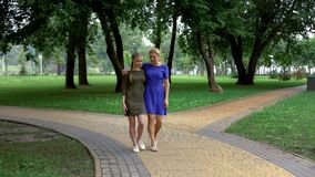 Mother and daughter walking along park chatting and laughing, pastime together. Stock photo royalty free stock image