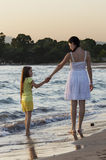 Mother and daughter walking along sea shore at sunset  Stock Photo