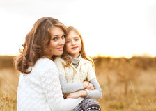 Mother and daughter walking in autumn in a field. Royalty Free Stock Image