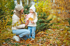 Mother and daughter walking in autumn park. royalty free stock photos