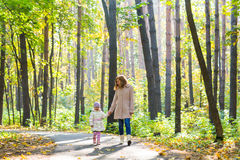 Mother and daughter walking in the autumn park Royalty Free Stock Images