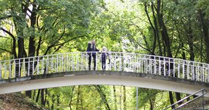 Mother and daughter are walking in the autumn park. A young woman with a little girl in identical jackets have fun on a walk on the bridge stock video