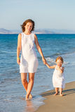 Mother and daughter walking on the beach Stock Photography